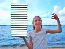 Meisje met een bos van boeken stock afbeelding