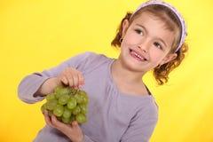 Meisje met een bos van druiven Stock Foto's