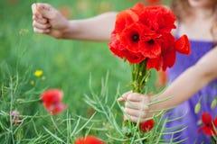 Meisje met een bos van rode papavers Royalty-vrije Stock Foto's