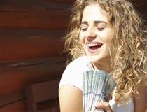 meisje met een bundel van geld dichtbij royalty-vrije stock afbeelding