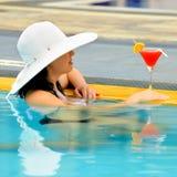 Meisje met een cocktail bij de rand van het zwembad Stock Foto's