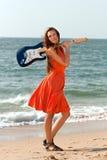 Meisje met een gitaar op het strand Stock Afbeelding