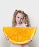 Meisje met een grote plak van sinaasappel in haar handen, als concept om beter en meer in het leven te bereiken Stock Afbeeldingen