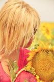 Meisje met een grote rijpe zonnebloem op het gebied stock afbeeldingen
