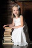 Meisje met een grote stapel boeken Stock Afbeeldingen