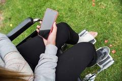 Meisje met een hand en een voet in een rolstoel wordt verbonden die Het mobiele telefoonscherm in zwarte op groen gras royalty-vrije stock afbeelding