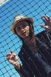 Meisje met een hoed achter een net royalty-vrije stock afbeeldingen