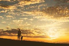 Meisje met een hond bij zonsondergang Stock Foto's