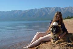 Meisje met een hond op de kust van Meer Baikal Royalty-vrije Stock Foto