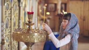 Meisje met een kaars die voor pictogrammen in de Orthodoxe Kerk bidden stock videobeelden