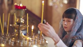 Meisje met een kaars die voor pictogrammen in de Orthodoxe Kerk bidden stock footage