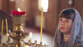 Meisje met een kaars die voor pictogrammen in de Orthodoxe Kerk bidden stock video