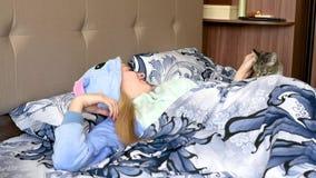 Meisje met een kat die die in bed liggen met een deken wordt behandeld stock videobeelden