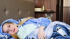 Meisje met een kat die die in bed liggen met een deken wordt behandeld stock footage