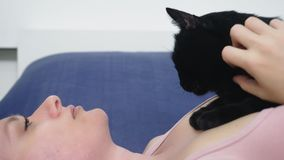 Meisje met een kat Mooi blondemeisje die in bed liggen en haar zwarte kat strelen Het geven voor dieren Liefde voor Huisdieren stock footage