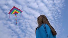 Meisje met een kleurrijke vlieger die in de blauwe hemel vliegen stock footage