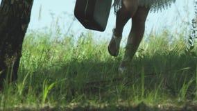 Meisje met een koffer die op het groene gras in wilde aard lopen stock footage