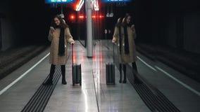 Meisje met een koffer op het platform van de metro stock video