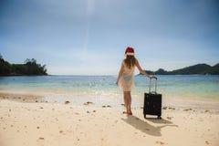 Meisje met een koffer op het strand royalty-vrije stock afbeelding