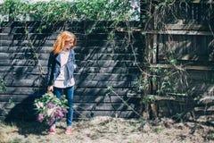 Meisje met een lilac boeket van sering in de tuin tearing meisje de sering in de tuin Stock Afbeeldingen