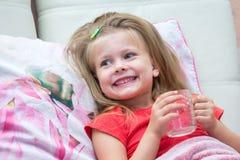 Meisje met een mok melk stock afbeelding