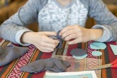 Meisje met een naald en een draad verwezenlijking het meisje naait stuk speelgoed dat van gevoeld wordt gemaakt verwezenlijking h royalty-vrije stock foto
