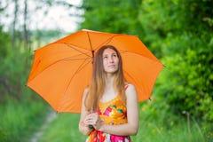 Meisje met een oranje paraplu stock afbeelding