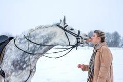 Meisje met een paard in de winter op sneeuw Royalty-vrije Stock Foto's