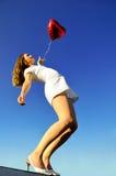 Meisje met een rode ballon in de vorm van hart stock afbeelding