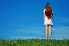 Meisje met een rode ballon in de vorm van hart stock fotografie
