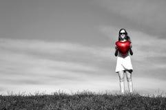 Meisje met een rode ballon in de vorm van hart stock foto's