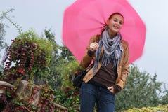Meisje met een roze paraplu Stock Foto's