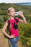 Meisje met een rugzak die zich op de achtergrond van het meer en het drinkwater bevinden Stock Fotografie