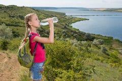 Meisje met een rugzak die zich op de achtergrond van het meer en het drinkwater bevinden Stock Afbeelding
