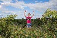 Meisje met een rugzak die zich op de achtergrond van het meer en het drinkwater bevinden Stock Afbeeldingen