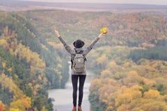 Meisje met een rugzak en een hoed die zich op een heuvel bevinden Omhoog opgeheven handen Rivier en hieronder bergen stock afbeelding