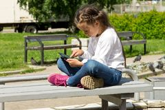 Meisje met een tablet in handen die in openlucht, aandachtig het tabletscherm bekijken royalty-vrije stock foto