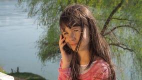 Meisje met een telefoon door het water Het kind is in openlucht Een meisje op een zonnige de lentedag door de rivier stock videobeelden