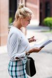 Meisje met een telefoon en document in handen Stock Foto