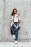 Meisje met een telefoon en een koffie ter beschikking Royalty-vrije Stock Foto