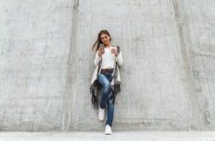Meisje met een telefoon en een koffie ter beschikking Royalty-vrije Stock Foto's
