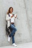 Meisje met een telefoon en een koffie ter beschikking Royalty-vrije Stock Fotografie