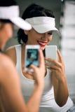 Meisje met een telefoon voor de spiegel Stock Afbeeldingen