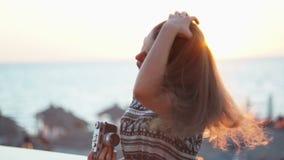 Meisje met een uitstekende camera Strand, zonsondergang, wind stock footage