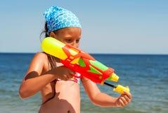 Meisje met een waterpistool op het strand Stock Afbeeldingen