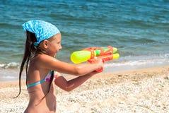 Meisje met een waterpistool op het strand Stock Afbeelding