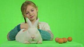 Meisje met een wit konijn op het groen scherm stock videobeelden