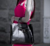 Meisje met een zak in een roze montagekleding stock afbeeldingen