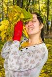 Meisje met esdoornbladeren Stock Afbeelding