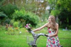 Meisje met fiets en bloemen in platteland Royalty-vrije Stock Afbeelding